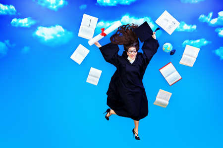 Happy graduate student is flying in the sky with her diploma and books  photo