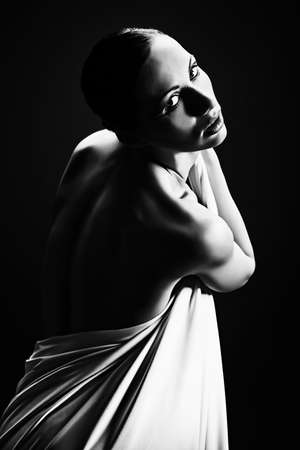 Art portrait of a beautiful  woman back over black background. photo