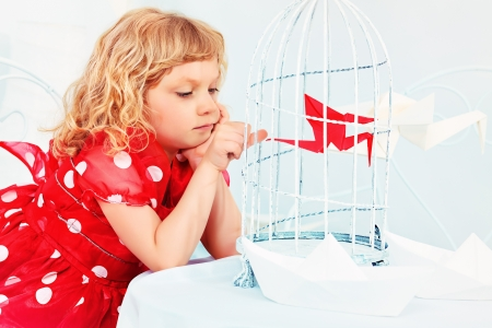 Portrait of a beautiful little girl holding birdcage with a red paper bird. photo