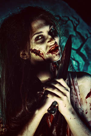 bloodthirsty: Bloodthirsty zombi with a knife standing at the night cemetery in the mist and moonlight.