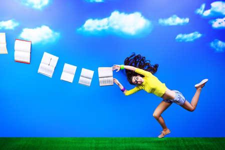 libros volando: Feliz niña estudiante está volando en el cielo con sus libros.