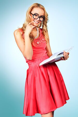 studing: Pretty blonde woman with a book posing at studio over grey background. Stock Photo