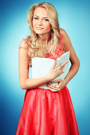 Pretty blonde woman with a book posing at studio over grey background. photo