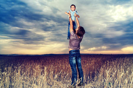 Happy father playing with his little son in the wheat field over beautiful cloudy sky.  photo