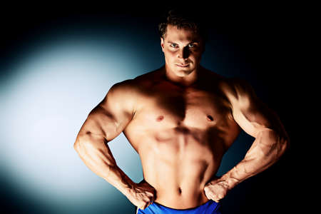 male male torso: Portrait of a handsome muscular bodybuilder posing over black background. Stock Photo