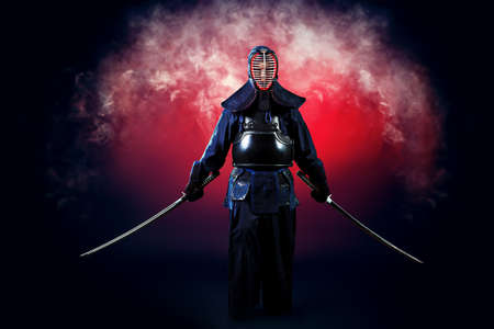 samurai warrior: Handsome young man practicing kendo. Over dark background. Stock Photo