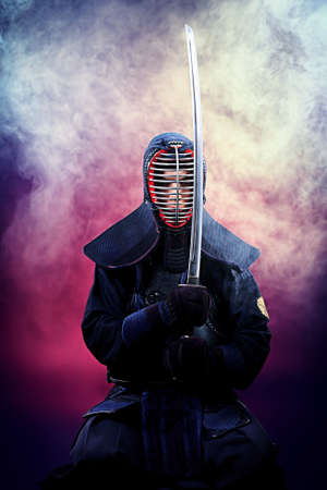 asian warrior: Handsome young man practicing kendo. Over dark background. Stock Photo
