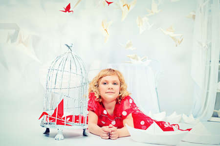 Portrait of a beautiful little girl lying on a floor with her birdcage with a red paper bird. photo