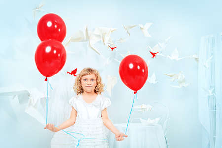 Cute little girl standing with red balloons in a white room surrounded with paper birds.  photo