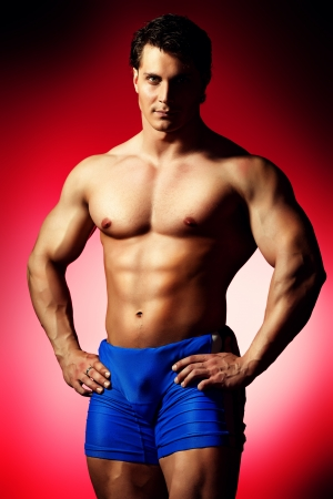 Portrait of a handsome muscular bodybuilder posing over red background. photo