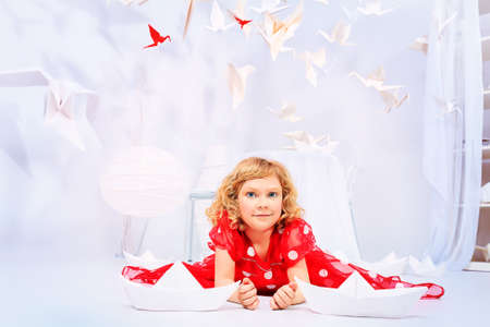 Beautiful little girl lying on a floor in her dream world surrounded with paper birds and ships. photo