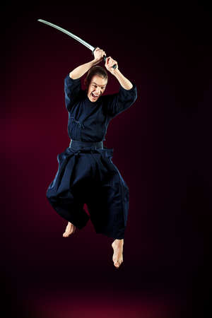 Handsome young man practicing kendo. Over dark background. photo