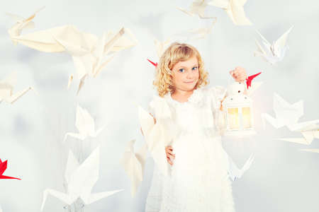 Beautiful little girl in her dream world surrounded with paper birds, holding a lamp. photo