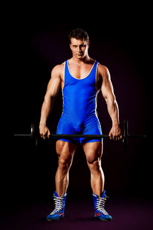 muscle guy: Portrait of a handsome muscular bodybuilder posing over black background. Stock Photo