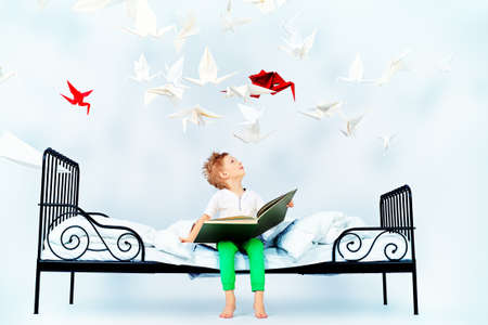 magic book: Cute little boy sitting on the bed and reading fairy tales. Dream world. Stock Photo
