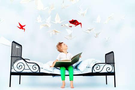 lezing: Schattige kleine jongen zittend op het bed en het lezen van sprookjes. Droomwereld.