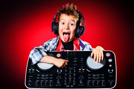 heavy metal music: Expressive little boy DJ in headphones mixing up some party music. Stock Photo
