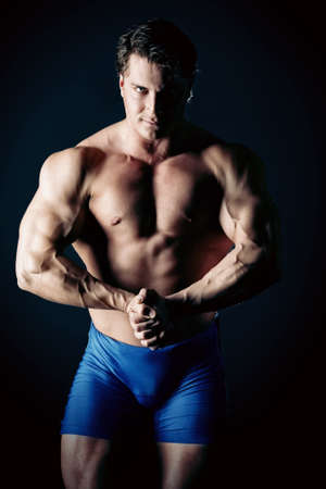 Portrait of a handsome muscular bodybuilder posing over black background. photo