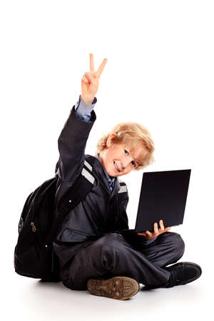 Happy schoolboy posing with his laptop. Isolated over white. photo