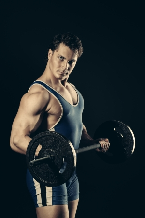 Portrait of a handsome bodybuilder posing over black background. photo