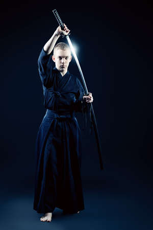 martial art: Handsome young man practicing kendo. Over dark background. Stock Photo