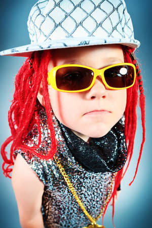 Portrait of a trendy little girl wearing red braids and modern clothes. photo