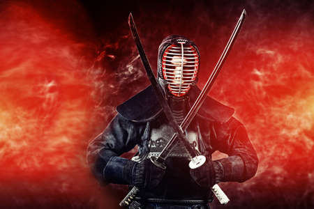 Young man practicing kendo. Over dark background.