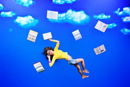 libros volando: Feliz ni?a estudiante est? volando en el cielo con sus libros.