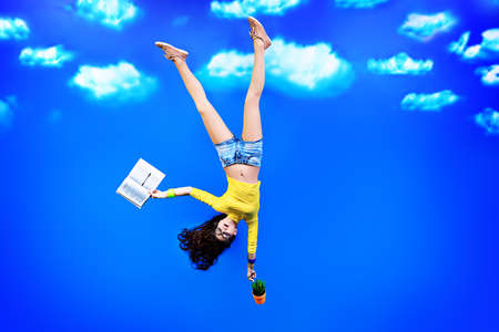Happy girl student standing upside down with a book over blue sky.