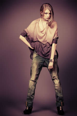 Beautiful fashion model posing at studio. Jeans style. photo