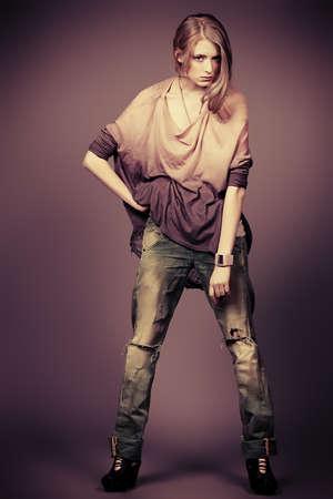 glamur: Beautiful fashion model posing at studio. Jeans style. Stock Photo