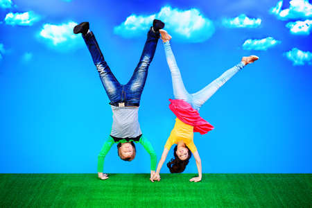 Couple of young people are standing on their heads on a green lawn over blue sky. photo