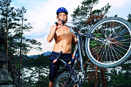 bicycle helmet: Young man cyclist holding his bicycle on the top of a hill.