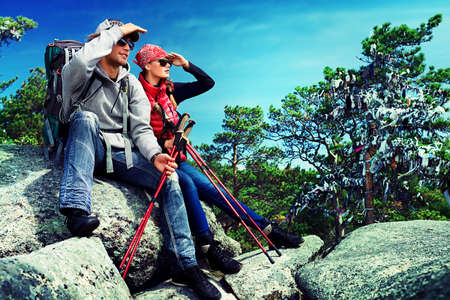 Couple of tourists are sitting at the top of a mountain and looking into the distance. photo