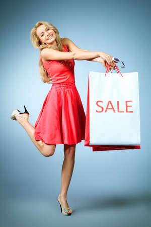 Portrait of a beautiful young woman carrying shopping bags  photo