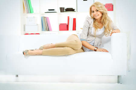 Portrait of a pretty blonde woman sitting on a sofa at home  photo