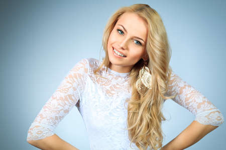 Portrait of a happy attractive young woman in white dress  photo