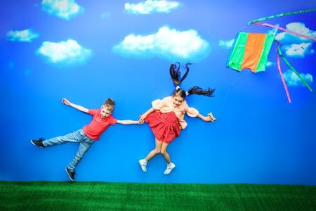 一起飞行在一个风筝的两个愉快的孩子在一个明亮的夏日