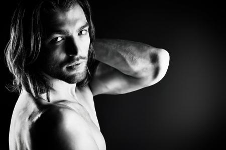 Portrait d'un homme musclé sexuelle posant sur fond sombre. Banque d'images - 20718661