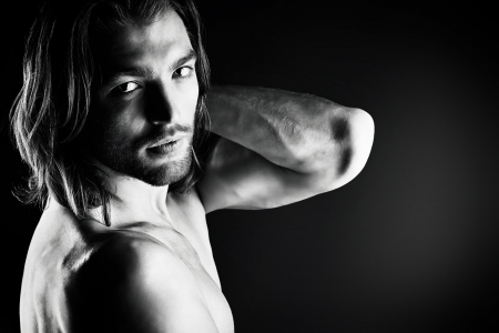 Portrait of a muscular man posing over dark background.