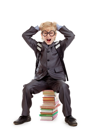 書籍のスタックの上に座って大きな丸眼鏡でショックを受けた男子生徒。白で隔離されました。 写真素材