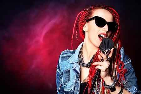 素晴らしい赤いドレッドヘアを持つヘッドフォンで表現力豊かな女の子。 写真素材