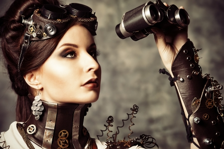 Portrait of a beautiful steampunk woman looking through the binoculars over grunge background. Imagens