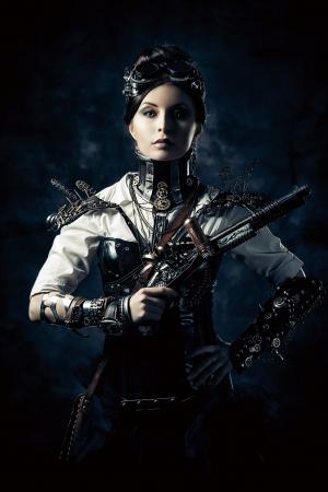 Portret van een mooie steampunk vrouw met een pistool op grunge achtergrond. Stockfoto