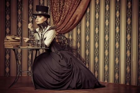 Portrait of a beautiful steampunk woman over vintage background. Reklamní fotografie