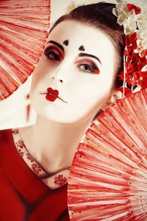 ファンと様式化された日本の芸者の芸術の肖像画。ボディ絵画プロジェクト。