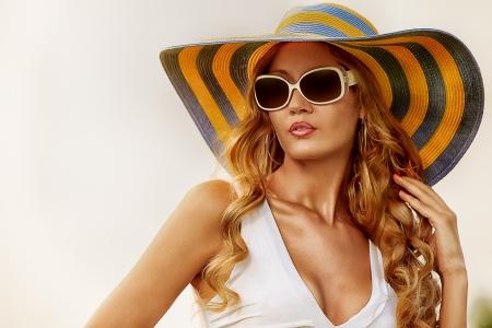 우아한 모자와 하늘에 포즈 선글라스에 아름 다운 젊은 여자.