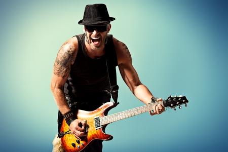 石の音楽家は、電気ギターを果たしています。 写真素材