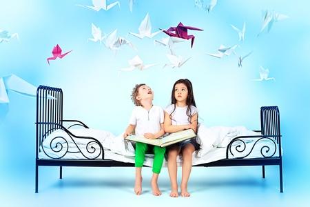 Nette Kinder sitzen zusammen auf dem Bett und liest Märchen. Traumwelt.