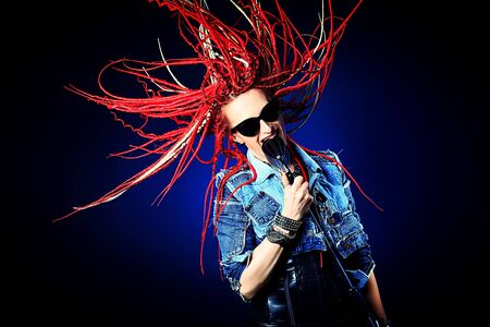 Modern rock singer singing into a microphone. Stock Photo - 21371891